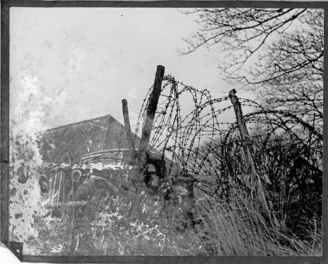WW2 car behind a barbed wire entanglement