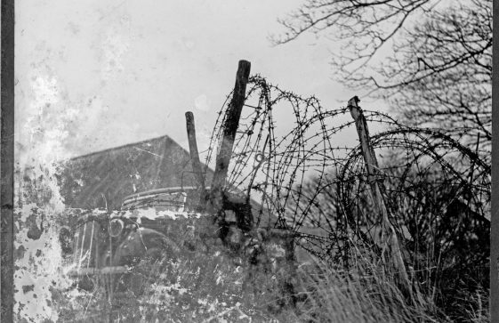 A WW II photo showing a WW II car behind a barbed wire entanglement