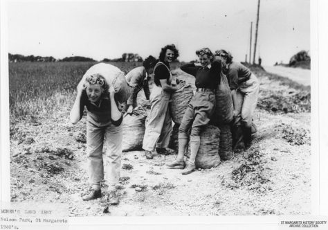 Miss Harrison and Women's Land Army landgirls carrying sacks of potatoes