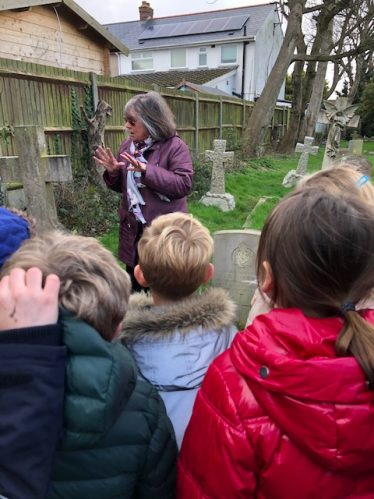 History Society volunteer Heather Berwick with children from the Primary School on a guided walk of the church and graveyard