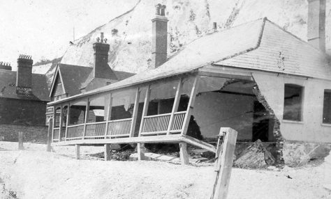 Storm damaged bungalow on the beach. c.1900