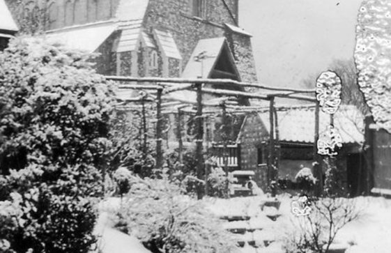 Garden and St Margaret's church tower in the snow.