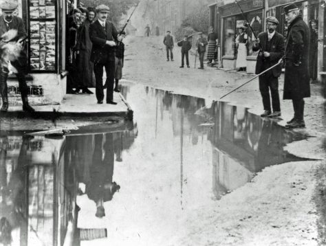 Photograph 'Fishing in the Flood' in High Street. December 1910
