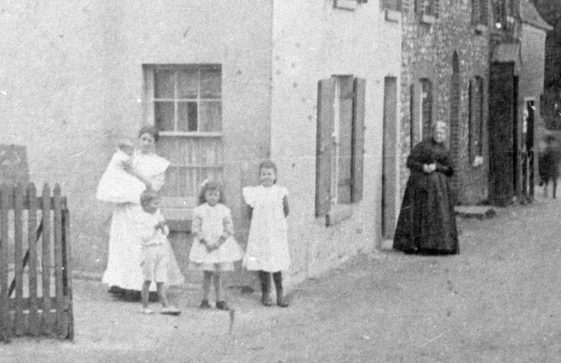 Family group in the High Street beyond Hope Inn. Date unknown