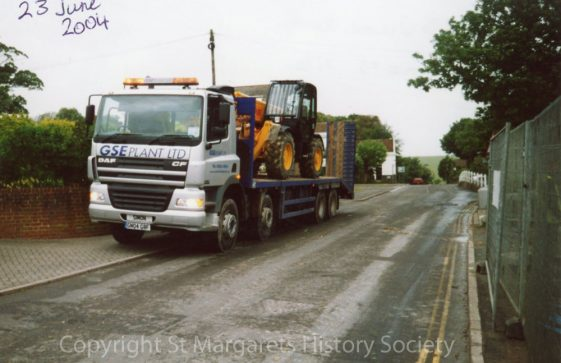 Low-loader lorry carrying construction equipment opposite Knoll Garage site, High Street. 23 June 2004.
