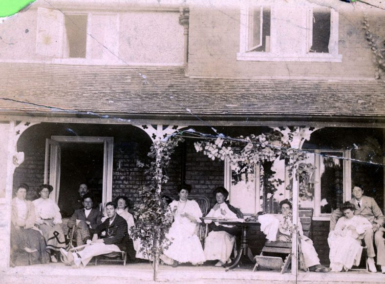 Group of people on a veranda; Playing bumble-puppy on the beach. c1907