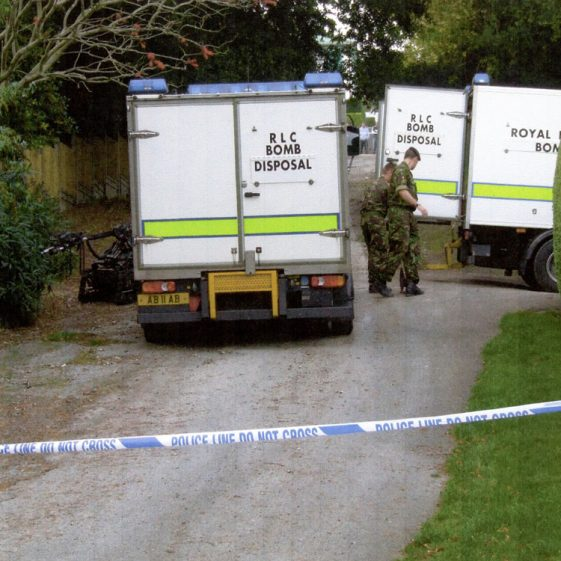 Bomb disposal vehicles, robot and personnel, and pieces of shrapnel following the find of explosives in the garden of 'The Moorings' 2009