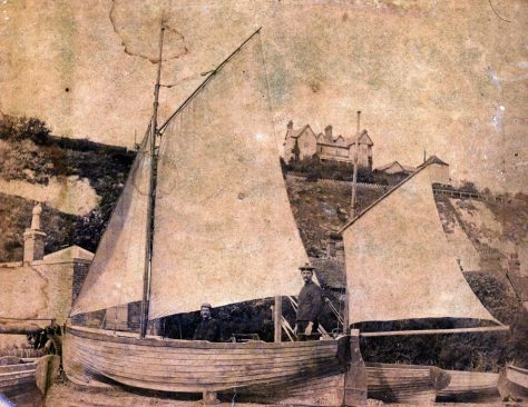 Two men standing in a small boat on the beach. c.1890