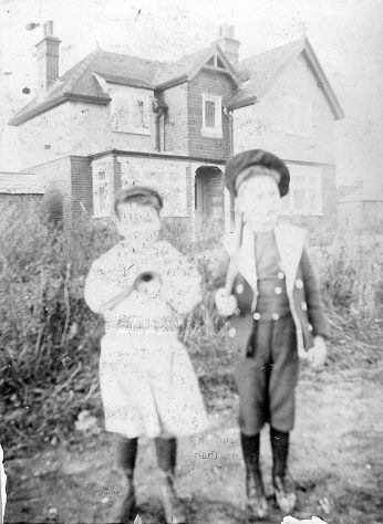 Two young boys in front of a house. c.1900