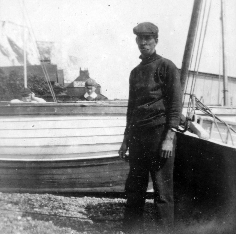 Boats and Jim Atkins on St Margaret's Bay beach. 1906